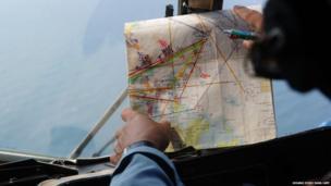 A Vietnamese crew member checks a map during a search flight