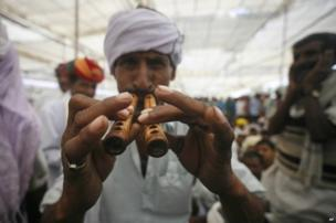 Indian village man plays a traditional wind instrument at an election campaign rally addressed by Congress party vice president Rahul Gandhi in Rajasthan.