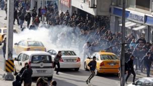 Demonstrators run from tear gas in Ankara (12 March 2014)