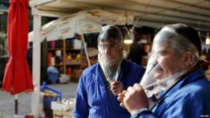 Men cover their heads in cling film to protect themselves from tear gas in Ankara (12 March 2014)