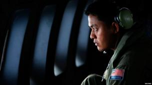 A crew member from the Royal Malaysian Air Force looks through the window of a Malaysian Air Force CN235 aircraft during a Search and Rescue (SAR) operation to find the missing Malaysia Airlines flight MH370, in the Straits of Malacca