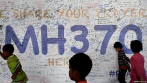 Children run past dedication messages on the walls of the Kuala Lumpur International Airport