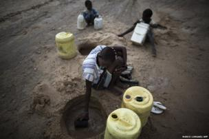 A Turkana woman scoops water from a dry river bed in Nasder, north of Lodwar in the Turkana region of Kenya