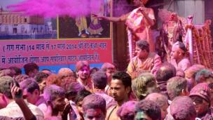 Indian devotees covered with coloured powder carry an idol of Lord Krishna (R) during Holi celebrations at the Durgiana Temple in Amritsar on 16 March 2014.