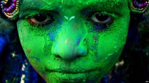 An Indian child adorned with coloured powder poses for a photograph while taking part in celebrations for the spring festival Holi in Bhubaneswar on 16 March 2014