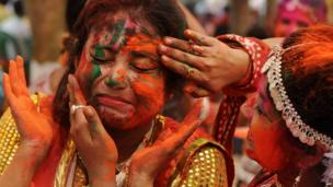 Indian revellers cover each other with coloured powder during celebrations for the Holi festival in Siliguri on 16 March 2014