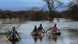 Pupils paddle across a swamp on reed-rafts in Kenya