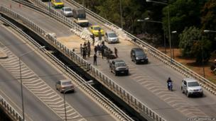 Cars pass through the site of a former road block after anti-government protesters remove the barriers in Bangkok, Thailand