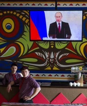 Staff at a pizza restaurant in Simferopol watch a speech by President Putin
