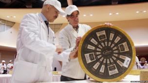 Roberto Castaneda (left) and Max McCalman inspect a wheel of gruyere