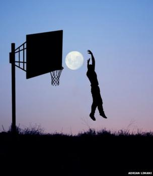 The silhouette of a man against the backdrop of the full moon in a purple sky. The silhouette of a basketball hoop is also visible. The man appears to be leaping into the air to 'slam dunk' the Moon into the net.