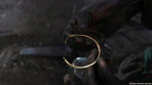 A blacksmith holds a bracelet made out of melted bullet casings at the Backsmith'smarket in Rumbek, South Sudan