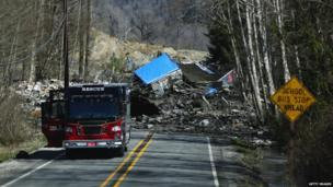 A road blocked by buildings uprooted and pushed down a hill by the landslide