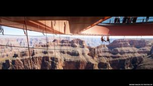 Technicians dangle from a series of ropes before cleaning the underside glass at Grand Canyon Skywalk in Arizona