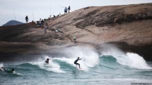 Surfers ride a wave near Arpoador Beach in Rio de Janeiro, Brazil