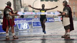 Two men dressed as centurions hold the banner of the finish line as Ethiopian Shume Hailu Legese wins the 20th Marathon of Rome on 23 March 2014