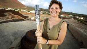 Ascension Heritage Society volunteer Helen Scott holds the Queen's Baton in Fort Hayes in Ascension Island