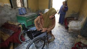 Mona Gama moves herself into her wheelchair in her home at the El'Arafa necropolis in Cairo (25 March 2014)