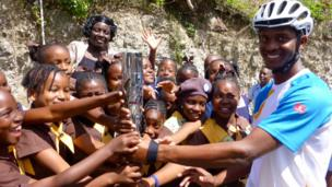 Barbados Cycling Team member Javed Mounter holds the Queen's Baton with a group of Brownies in Barbados.