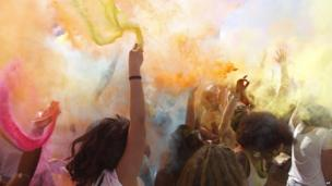 People throw colour powder in the air in Cape Town, South Africa, on 21 March 2014