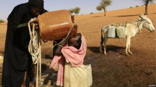 A girl is helped by her sister as she drinks water in Mellit town in Darfur on 24 March 2014