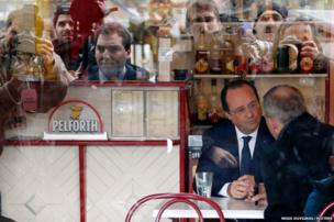France's President Francois Hollande is seen speaking in a bar after voting in the first round in the French mayoral elections in Tulle, central France