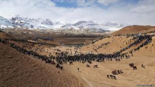Afghan horsemen and spectators gather on an arid patch of land near snow-capped mountains to play the traditional sport of Buzkashi near Bamiyan city in central Afghanistan