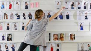 An employee organises photographs of models at the Asos headquarters