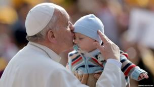 Pope Francis kisses a baby