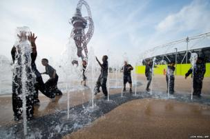 Children play in the fountains in front of the ArcelorMittal Orbit tower in the Queen Elizabeth Olympic Park, east London