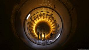 Iraqi workers clean furnace pipes at a cement plant in Najaf, south of Baghdad