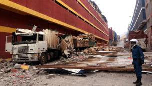 Lorries destroyed by parts of a building that fell off after the quake and its aftershocks hit Iquique - 3 April 2014