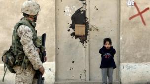 An Iraqi girl covers her ears as a US Marine patrols the Iraqi town of Falluja. Photo: 2005