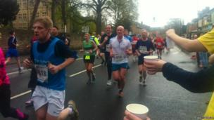 Water being offered to Sheffield runners.