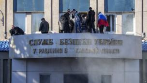 Pro-Russian activists stand on the balcony of the Ukrainian regional office of the security service in Luhansk, Ukraine, on 6 April 2014