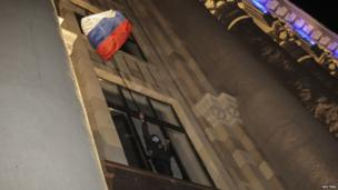 A protester waves a Russian flag out of a window of a seized regional administrative building in Kharkiv on 6 April 2014