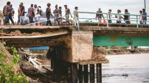 Pedestrians walk across a bridge damaged as a result of severe flooding near the capital Honiara in the Solomon Islands in this picture released by World Vision on 6 April, 2014