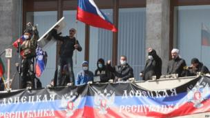 """Pro-Russian protesters who seized the main administration building in the eastern Ukrainian city of Donetsk wave a flag of their """"people's republic"""", the Donetsk Republic, and hold a Russian flag."""