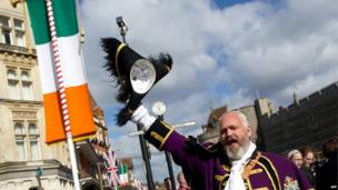 A town crier shouts and waves his hat