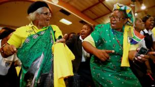 Supporters of South Africa's governing African National Congress (ANC) dance and sing in Wentworth township, outside of Durban, on 9 April 2014