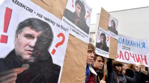 """Protesters hold placards depicting acting Ukrainian Interior Minister Arsen Avakov reading """"Avakov - whose side are you on? Either stop separatists or get out!"""" during their protest action at the ministry in Kiev on 14 April 2014"""