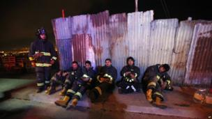Firefighters take a break from battling blazes in the city of Valparaiso on 14 April 2014