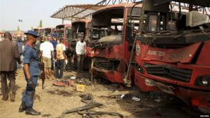 Bomb experts search for evidences in front of damaged buses at Nyanya in Abuja on 14 April 2014.