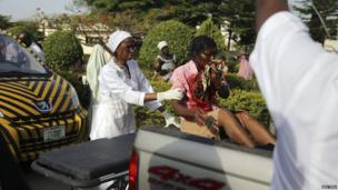 A nurse helps an injured bomb victim sitting at the back of a pickup truck at the Asokoro General Hospital in Abuja, on 14 April 2014.