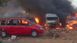Vehicles burn after an attack at a bus station in Abuja on 14 April 2014.