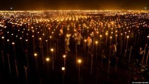 Volunteers light candles