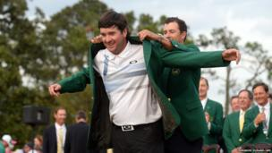 Adam Scott of Australia presents Bubba Watson of the US the Masters winner's green jacket