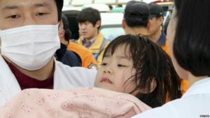 """A girl rescued by South Korean maritime policemen from a sinking ship """"Sewol"""" in the sea off Jindo, is treated at a port in Jindo April 16, 2014"""