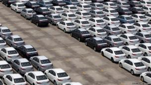 A man walks among cars which are ready for export at the port of Taipei, northern Taiwan