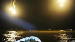 This handout photo by the South Korea Coast Guard taken at sea some 20 kilometres off the island of Byungpoong in Jindo on 17 April, 2014 shows coast guard members searching for passengers near a South Korean ferry that capsized on its way to Jeju island from Incheon